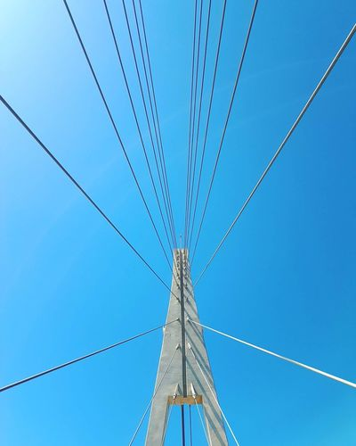 Looking up at a bridge against a clear blue sky