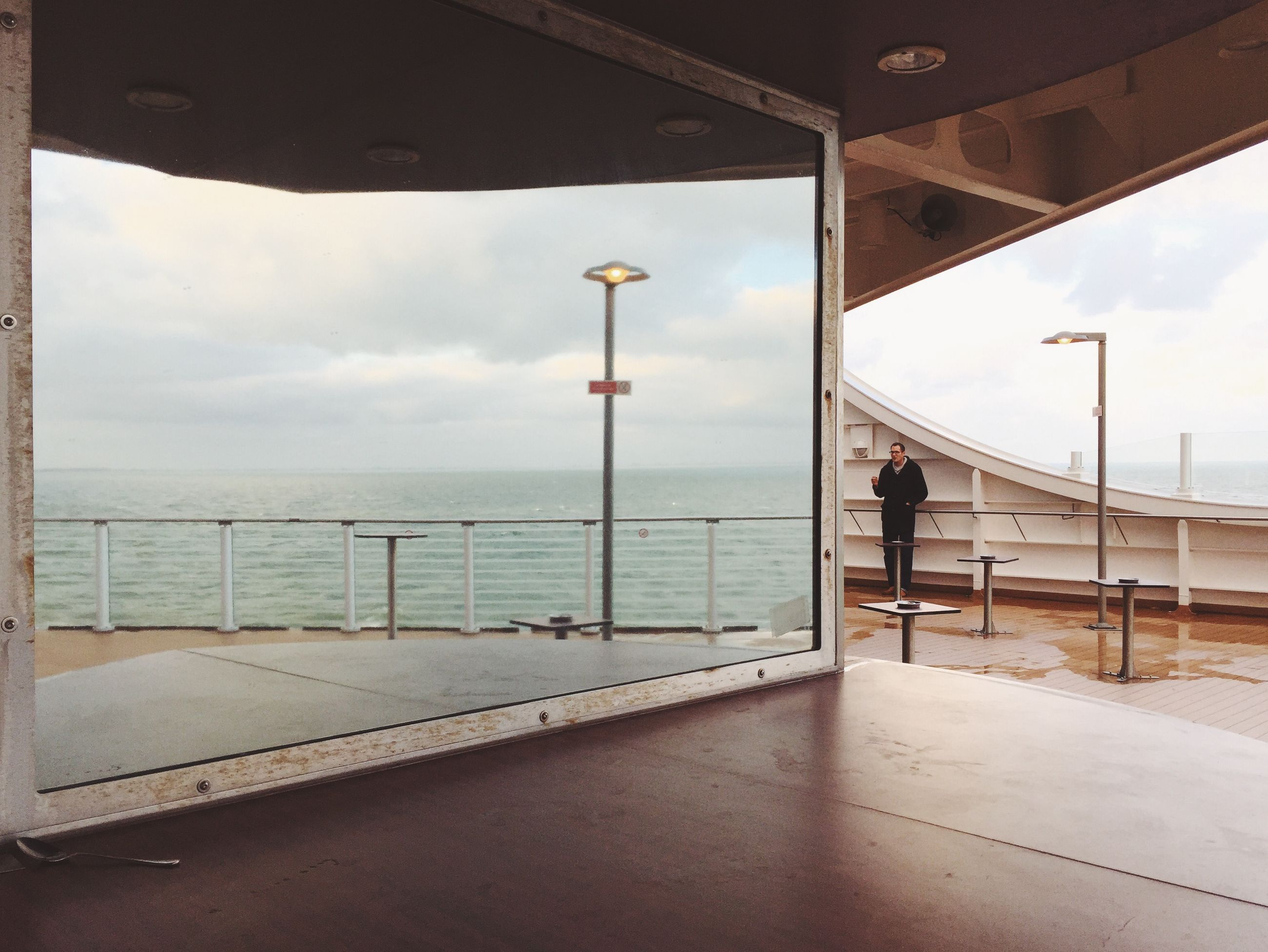sea, sky, horizon over water, water, men, railing, lifestyles, built structure, leisure activity, rear view, indoors, architecture, cloud - sky, full length, standing, person, street light, walking