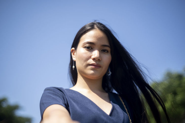 Portrait of a beautiful young woman against blue sky