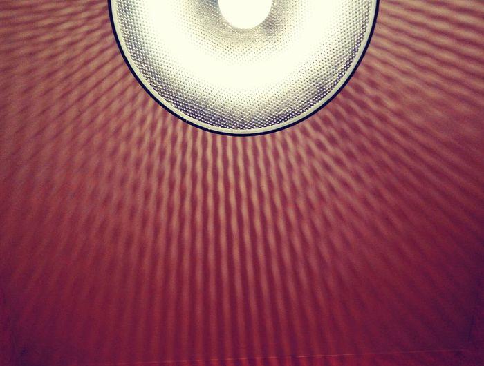 Cropped image of illuminated bulb in lamp shade