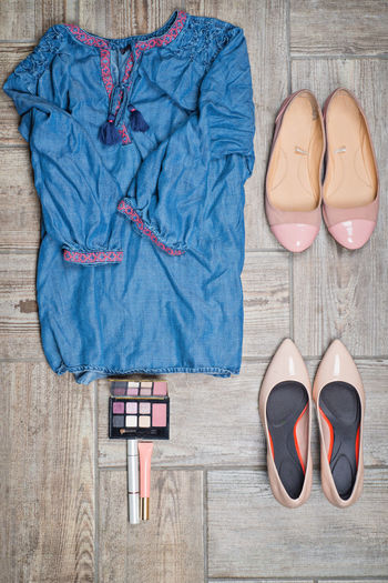 Flat lay of clothes with shoes and cosmetics on hardwood floor