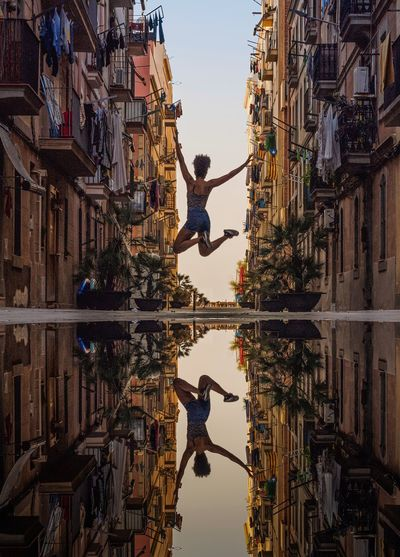 Low angle view of people walking on buildings in city