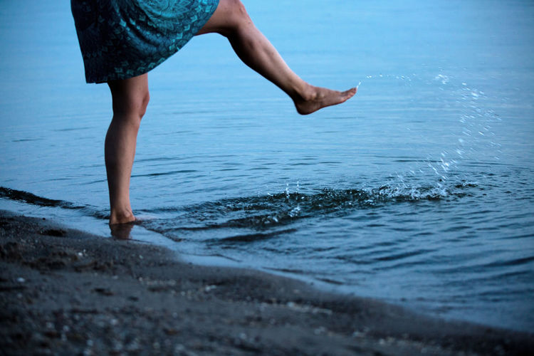 Low section of woman splashing water in sea at beach