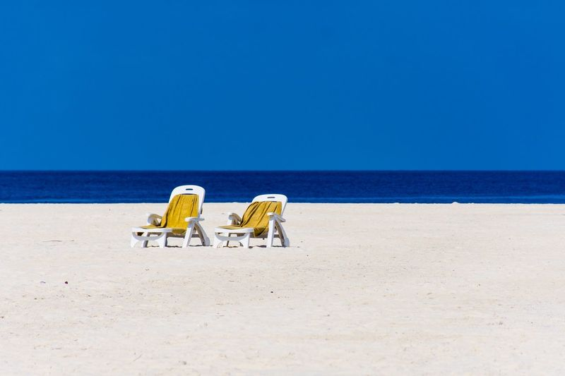 Deck chairs at beach against clear blue sky
