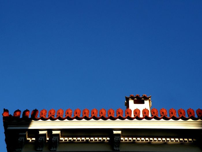 High section of built structure against clear blue sky