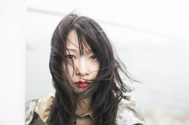Close-up portrait of woman with hair blowing in wind