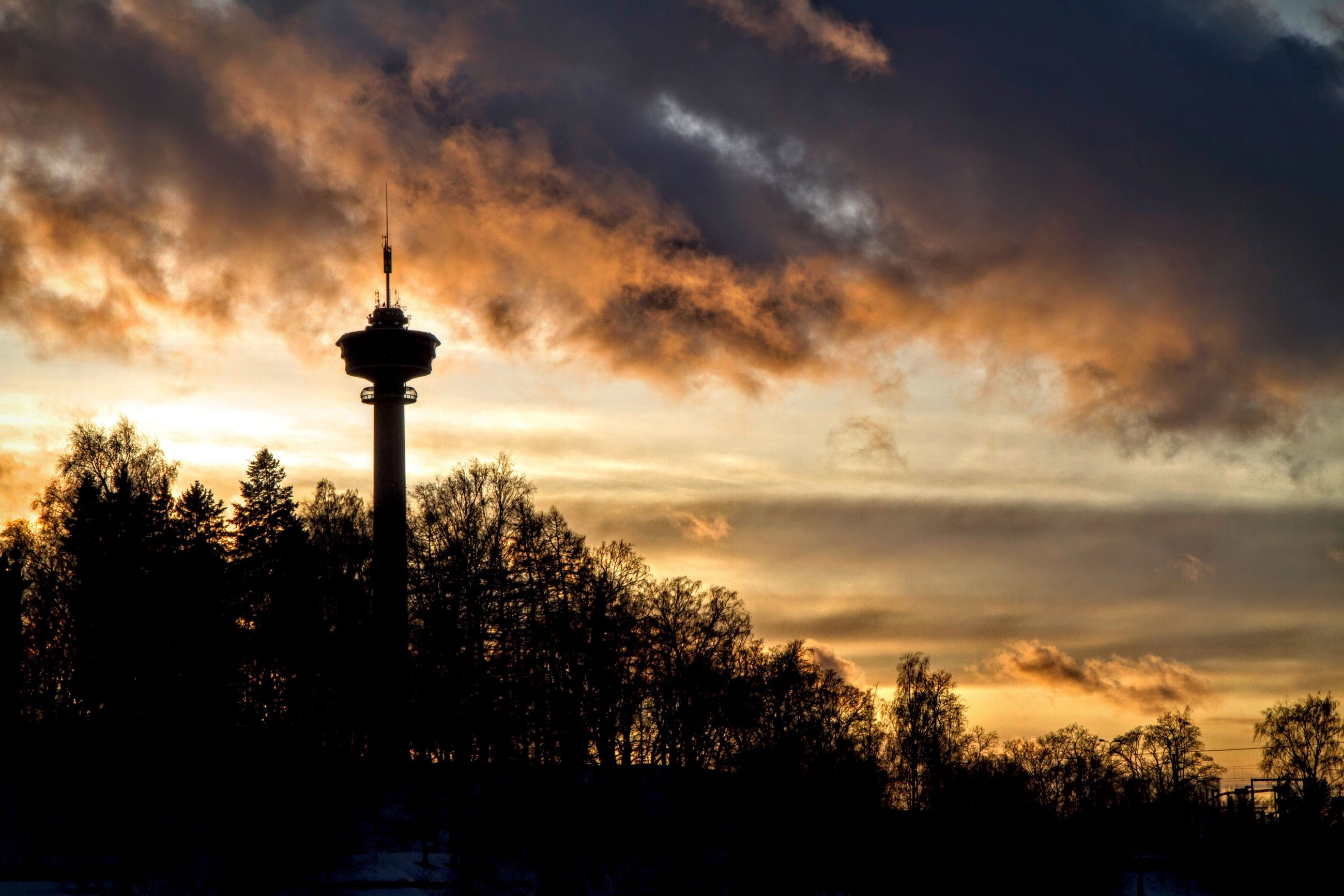 sky, cloud - sky, tree, sunset, silhouette, communications tower, cloudy, street light, tower, low angle view, built structure, cloud, architecture, dusk, building exterior, tall - high, dramatic sky, overcast, weather, nature