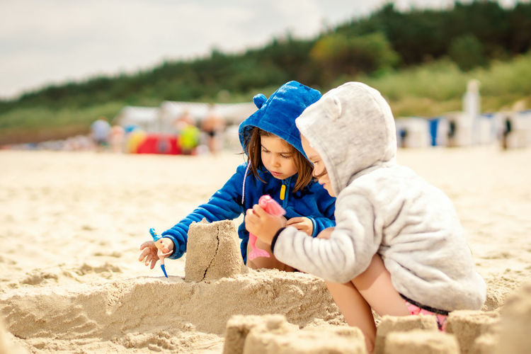 Sisters making sandcastle at beach