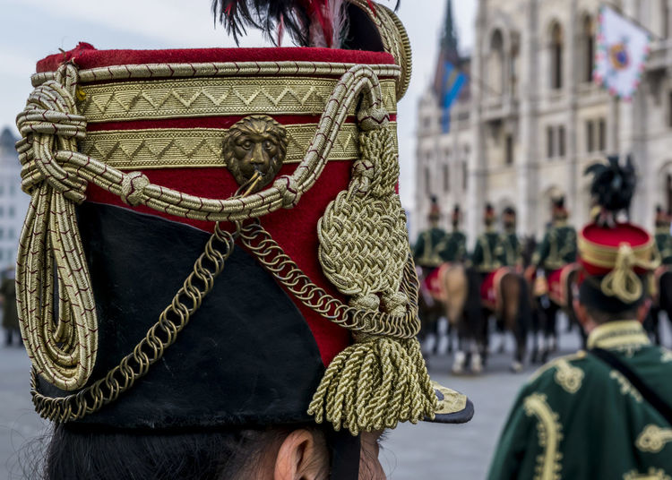 Hussar traditional military hat closeup. Background with line up of hussar cavalry on horses in front of the Parliament House during the 15 March military parade in Budapest, Hungary. Hungarian National Holiday. 15 March Budapest Hat Holiday Horses Hungary National Soldier Uniform Background Cavalry Close-up Clothing Costume Day History House Hungarian Hussar Military Outdoors Parliament People Person Traditional
