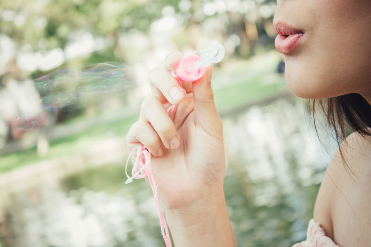 Close-up of woman holding pink flower