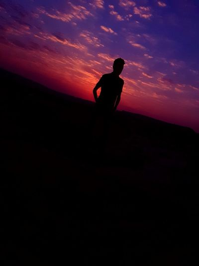 Silhouette Man Standing On Landscape Against Sky At Sunset