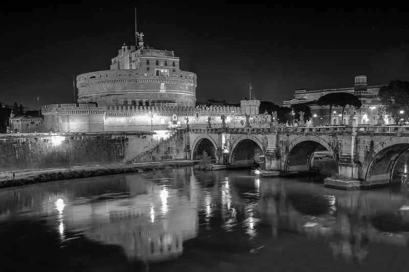 Reflection of historical Castel Sant'Angelo in Rome on the river in black & white Black And White Photography Reflection In The Water Tourist Spot Tourist Destination Tourist Attraction  Relection On Water Castle By The Riverside Rome Ancient Prison Rome Ancient Building Rome Ancient Castle Rome Landmark Castel Sant'Angelo Rome Black & White Architecture Night Built Structure Reflection Illuminated Water Building Exterior History Sky Outdoors Bridge - Man Made Structure No People Clear Sky City Arch EyeEmNewHere