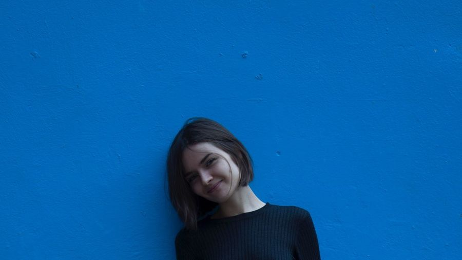 Portrait of young woman smiling while standing by blue wall