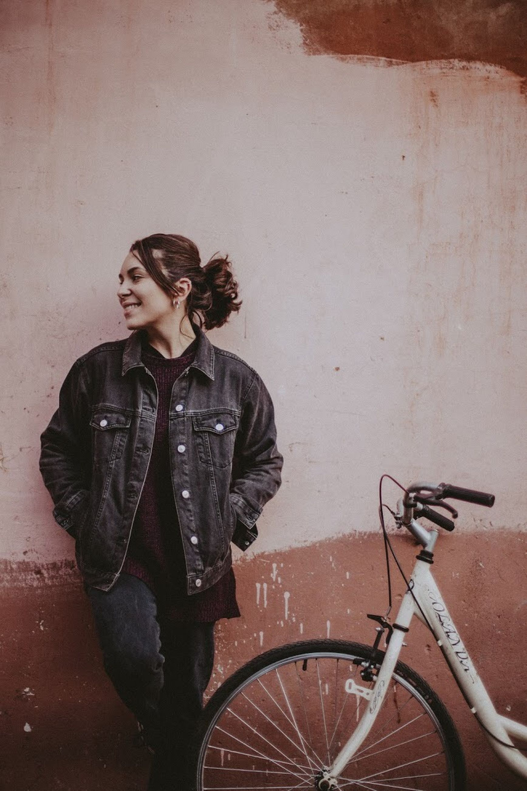one person, young adult, wall - building feature, bicycle, casual clothing, young women, real people, three quarter length, leisure activity, standing, transportation, lifestyles, front view, jacket, looking away, beauty, clothing, beautiful woman, hairstyle, leather jacket, leather, contemplation