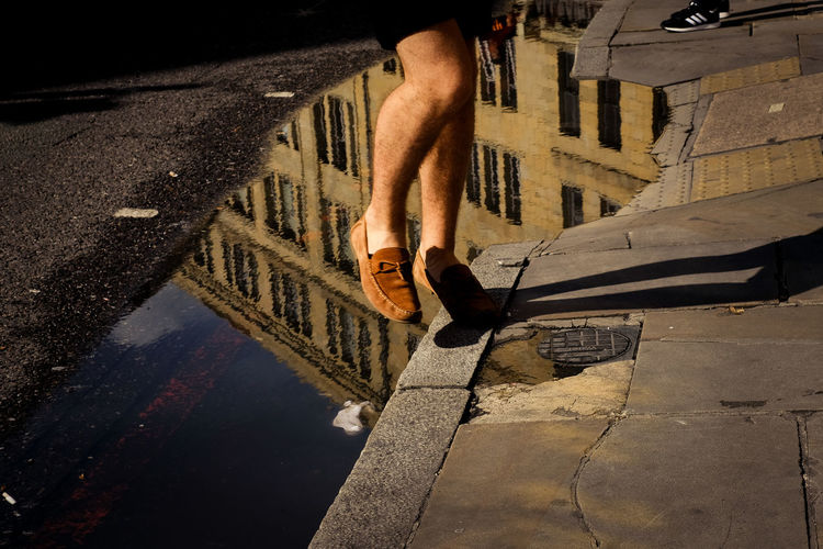 Low section of man in puddle on street