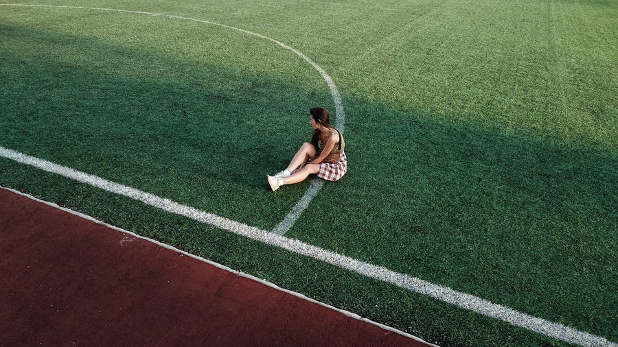 Young woman sitting on sport field