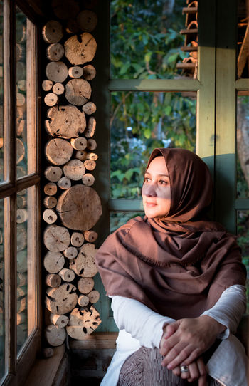 Thoughtful woman wearing hijab looking through window while sitting at home