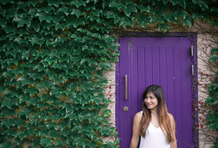 an Asian lady with long hair standing against a violet door with green leaf vine on cement house Architecture Beautiful Woman Building Exterior Built Structure Day Door Entrance Front View Hair Hairstyle Leisure Activity Lifestyles Long Hair Looking At Camera One Person Outdoors Portrait Real People Southeastasia Standing Violet Door Waiting Women Young Adult Young Women