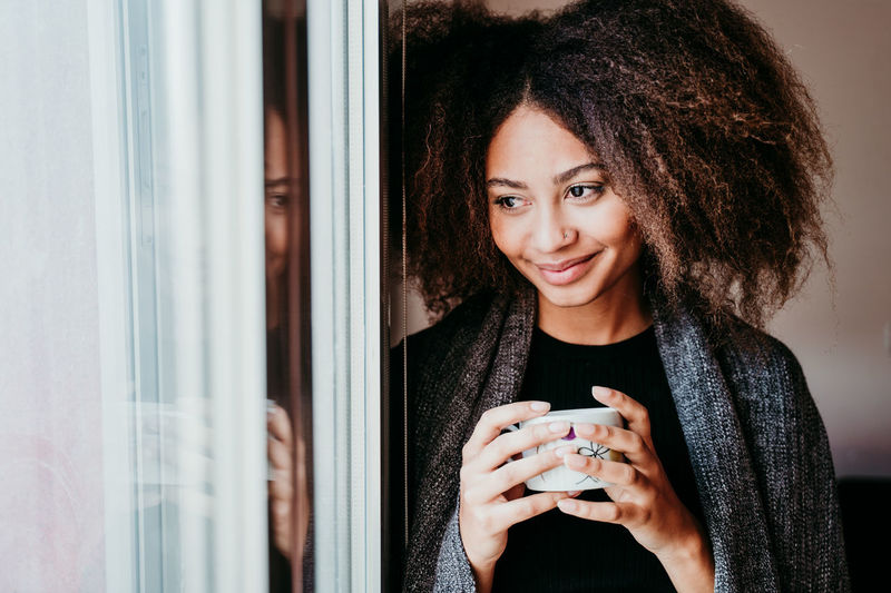 Smiling young woman holding coffee cup by window