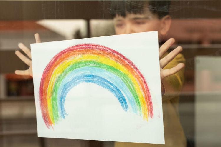 Boy holding multi colored rainbow painting seen through window