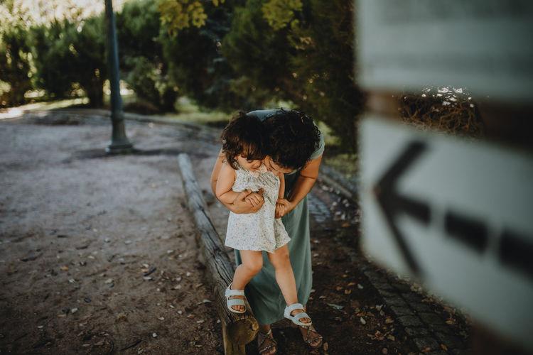 Woman having fun with daughter on sidewalk