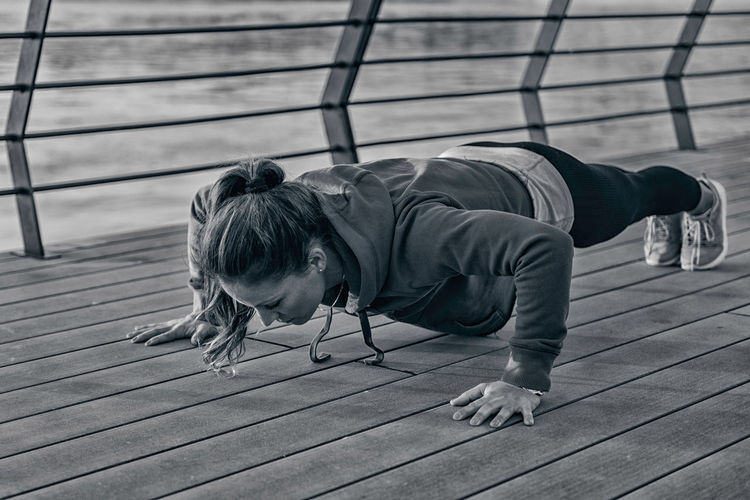 Woman Doing Plank on Riverside Urban Scene Lifestyle Sport Physical Activity Motion Effort Outdoors City Riverside River Exercising Workout Action Energy Sports Clothing Athlete City Life Healthy Lifestyle One Person Sports Training Black And White Day Plank Planks