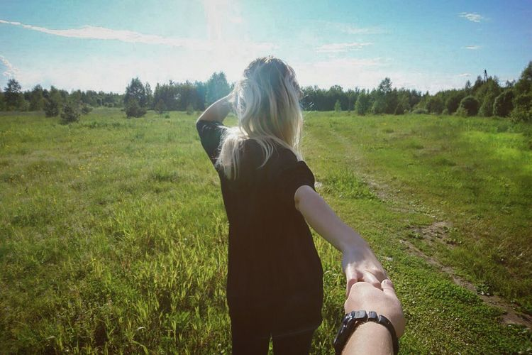 Cropped image of man holding girlfriend hand at park