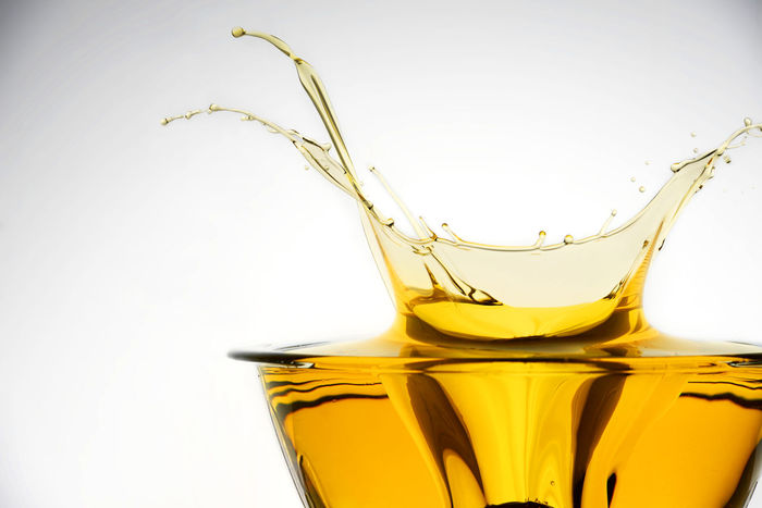 Side view of cooking oil splashing in container, studio background. Container Cooking Flows Fluids Gold Golden Light Liquid Olive Overflow Bowl Drop Droplets Lubricant Lubrication Oil Petrol Poured Spilling Splash Splashes Splashing Stream Transparent Yellow