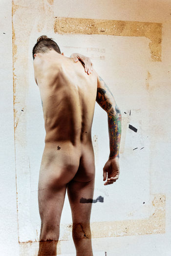 Rear view of shirtless man standing against wall