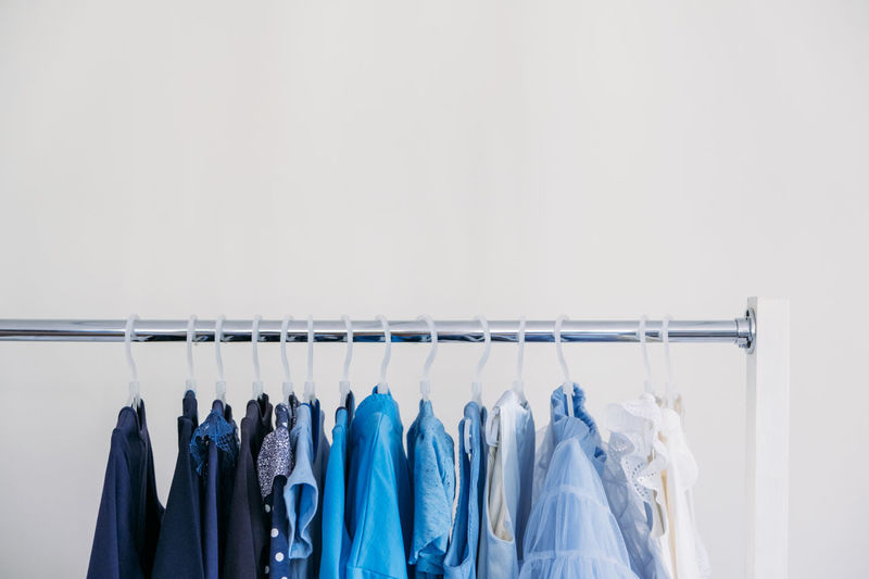 Fast fashion, sustainable fashion, minimalist wardrobe. variety of female blue clothing on hanging