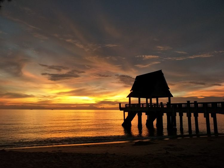 Getty image at the beach afterglow EyeEm Selects Sea Sunset Beach Water Hut Stilt House Built Structure Nature Sky Travel Destinations Architecture Horizon Over Water Beauty In Nature