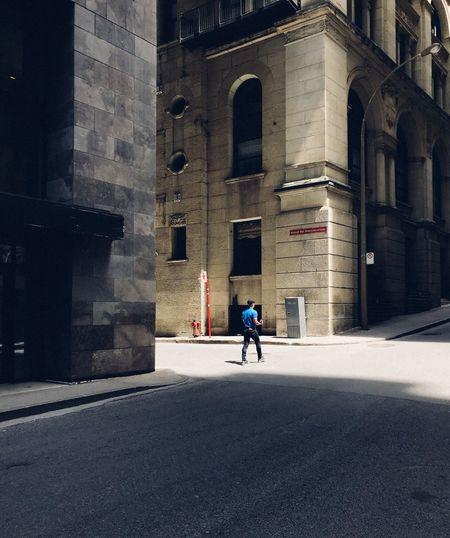 Man walking on road along buildings