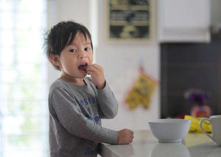 Portrait Of Boy Eating Food In Kitchen