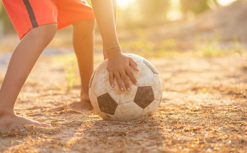 Low section of person playing soccer ball