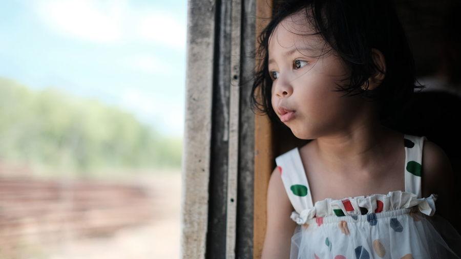 Cute girl looking through window in train