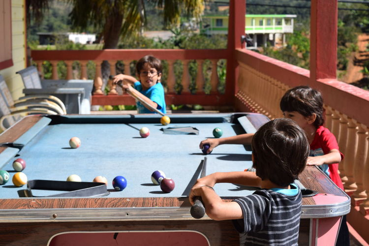 Cute children playing pool at porch