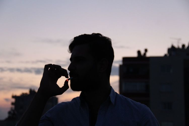Man smoking cigarette against sky during sunset