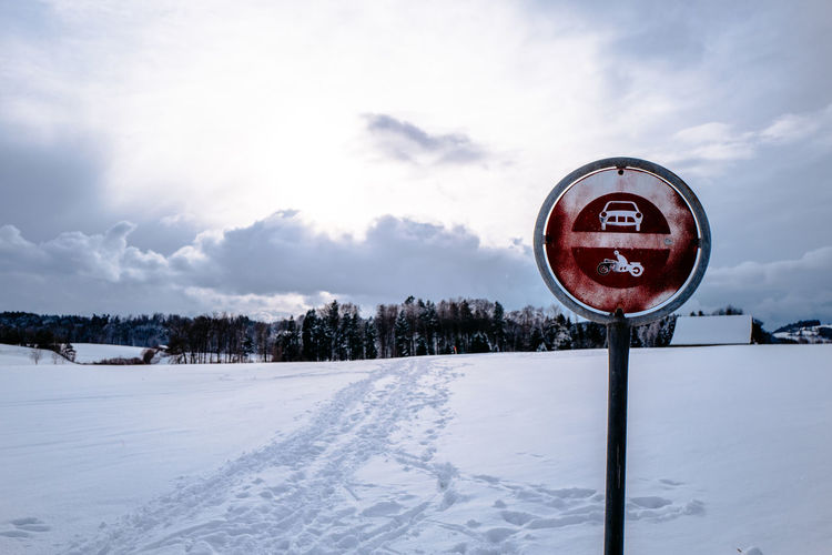 Metallic Sign On Snow Covered Road Against Cloudy Sky
