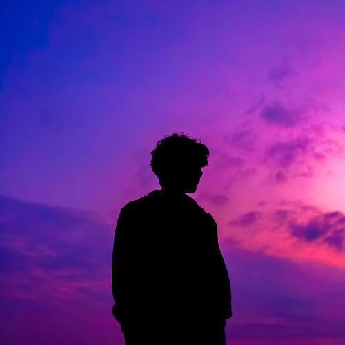 Silhouette man standing against dramatic sky