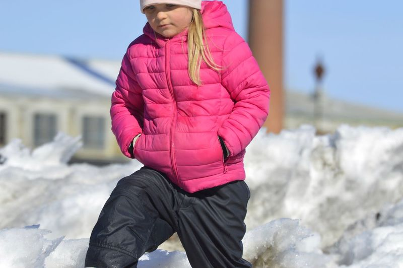 Girl Walking On Snow Covered Field