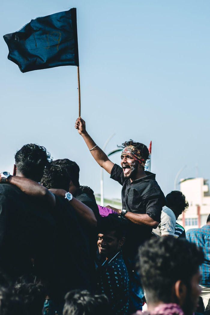 Man holding flag while screaming against sky