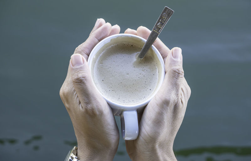 Close-up of hand holding coffee cup