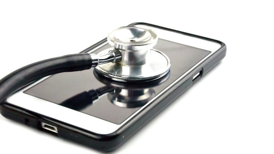 Close-up of stethoscope and mobile phone on table