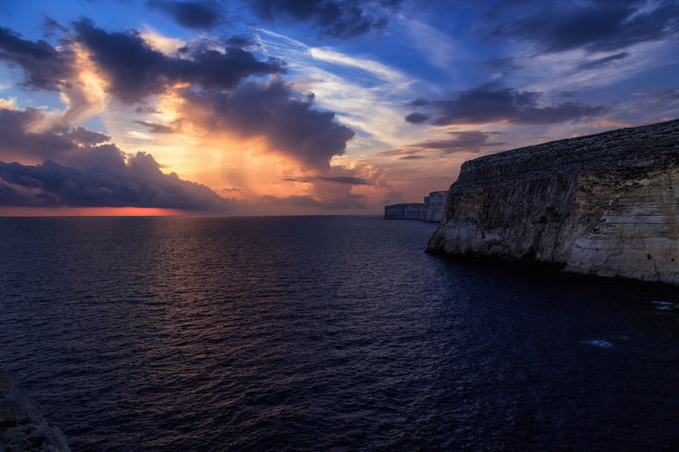 Scenic view of cliff at sea shore against cloudy sky during sunset