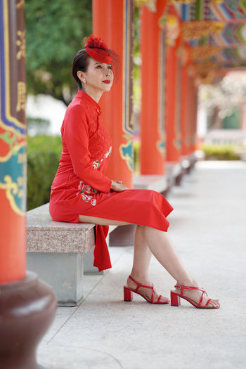 Midsection of woman in red traditional clothing sitting outdoors