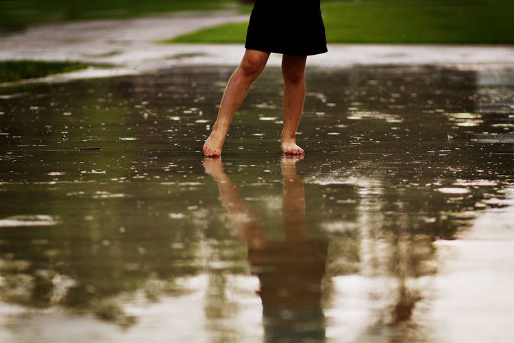 Low section of woman standing on wet road