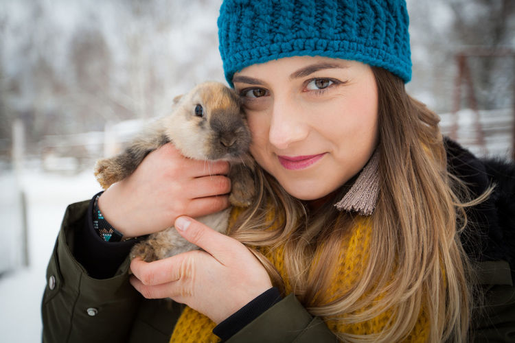 Artistic and natural portrait of beautiful woman in the nature. Woman Face Portrait Beautiful Beauty Smile Female Girl Young Hair Natural Nature Outdoors Skin White Happy Attractive Background Lifestyle Fashion Cute Winter Bunny  Pet Animal Hat Smiling One Person Clothing Looking At Camera Warm Clothing One Animal Emotion Headshot Happiness Pets Front View Women Mammal Domestic Positive Emotion Hairstyle Pet Owner