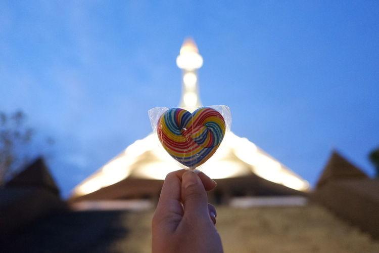 Person holding lollipop against blue sky