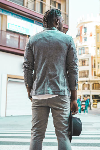 Rear view of man walking on street against buildings
