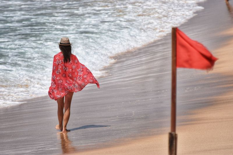 Red Flag One Person Patriotism Nature Water Clothing Leisure Activity Sea Women Sunlight Wind Rear View Full Length Outdoors Lifestyles